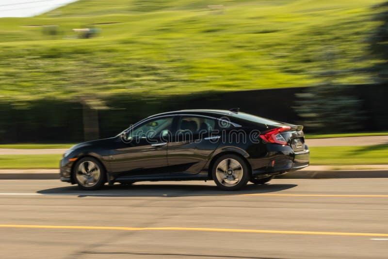 Przyśpieszać czarnego pełnych rozmiarów sedan w ruchu zdjęcie royalty free