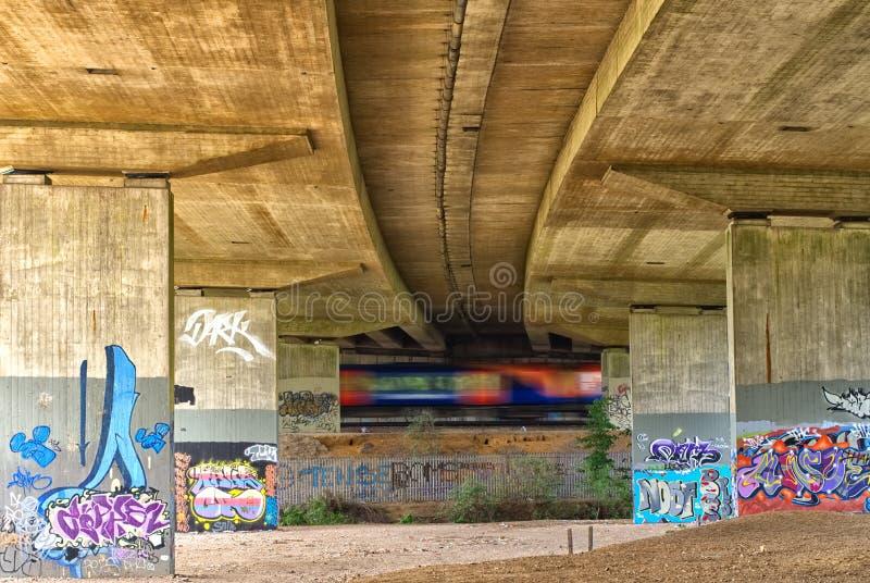 Przyśpieszający taborowe przepustki przez graffiti zakrywających bridżowych poparć, pod M25 autostradą fotografia royalty free