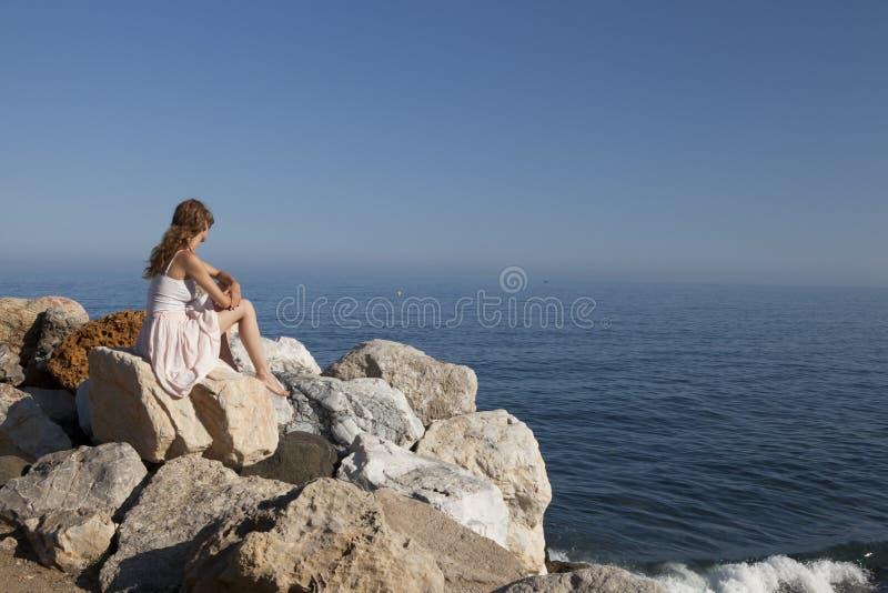 Przy dennym młodej kobiety obsiadaniem na skale obrazy stock