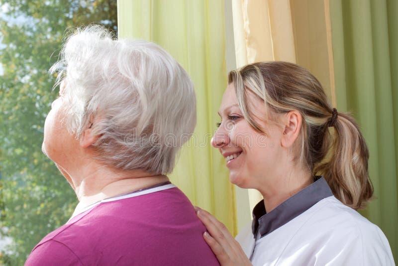 Przy okno pielęgniarki i starej kobiety pozycja zdjęcie stock