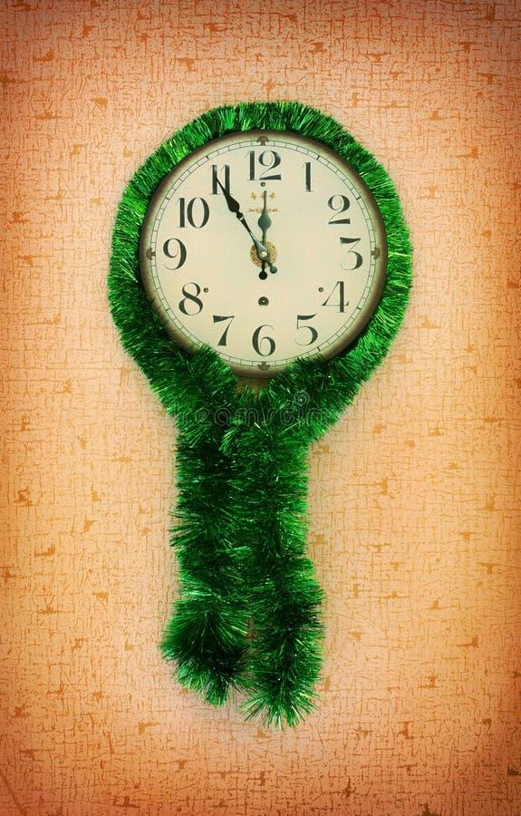 Przy pięć minutami dwanaście na starym ściennym zegarze dekorował z zielonym świecidełkiem obraz royalty free