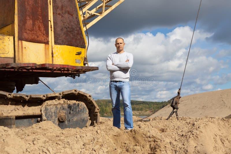 Przy piasek jamą ciągnikowy operator zdjęcie royalty free
