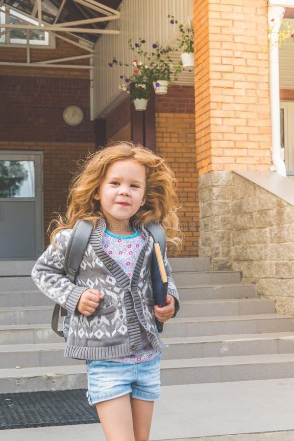 Przy recesją przy szkolną dziewczyną, dziecko out, przy lunchem z książką fotografia stock