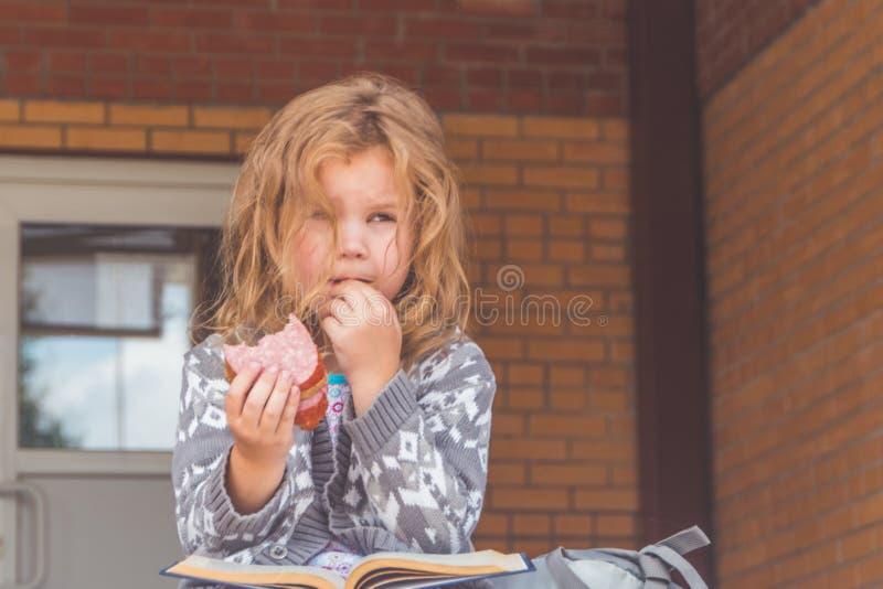 Przy recesją przy szkolną dziewczyną, dziecko out, przy lunchem z książką obrazy royalty free