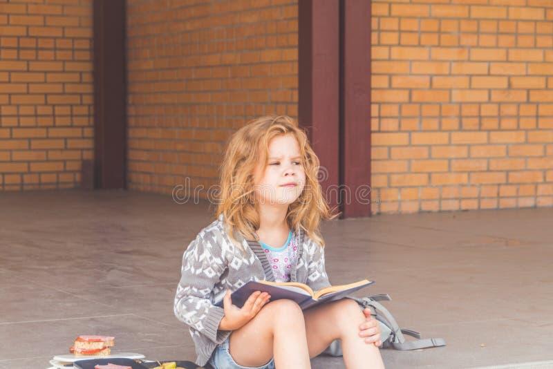 Przy recesją przy szkolną dziewczyną, dziecko out, przy lunchem z książką obrazy stock