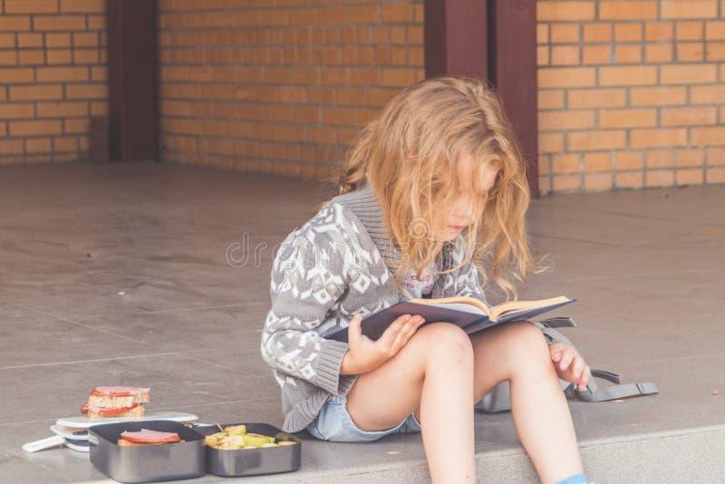 Przy recesją przy szkolną dziewczyną, dziecko out, przy lunchem z książką obraz stock