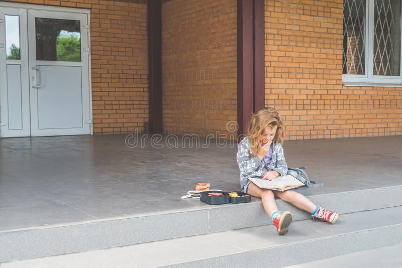Przy recesją przy szkolną dziewczyną, dziecko out, przy lunchem z książką obraz royalty free