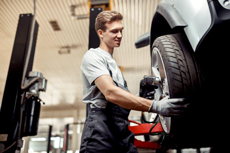 Przy samochodową remontową usługą automechanic zmiany opona podczas gdy przy pracą fotografia royalty free