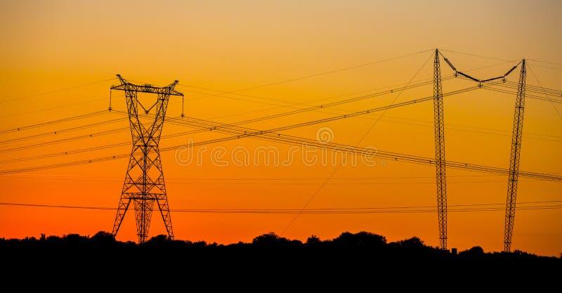 Przy zmierzchem elektryczność pilony obraz stock
