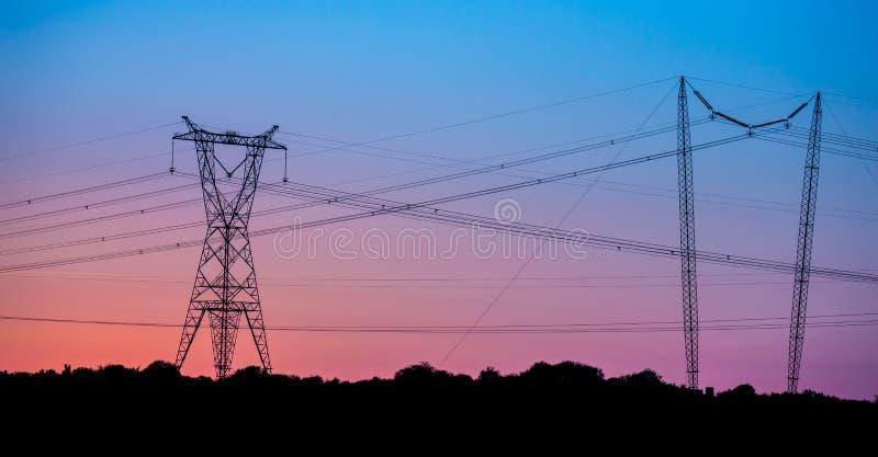 Przy zmierzchem elektryczność pilony fotografia royalty free