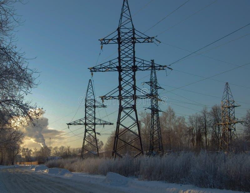 Przy zmierzchem w zimie, wysokonapięciowy poparcie fotografia stock