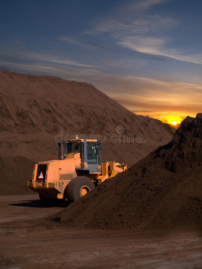 Przy zmierzchu wschód słońca glebowi Backhoe i Wierzchołka wielcy stosy zdjęcie stock