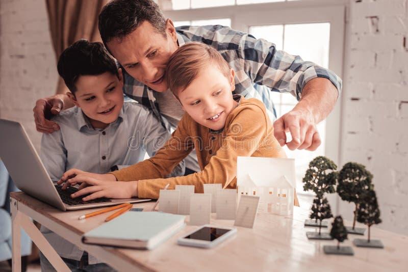 Przybrany ojciec pokazuje ich dzieciom edukacyjnego wideo zdjęcia royalty free