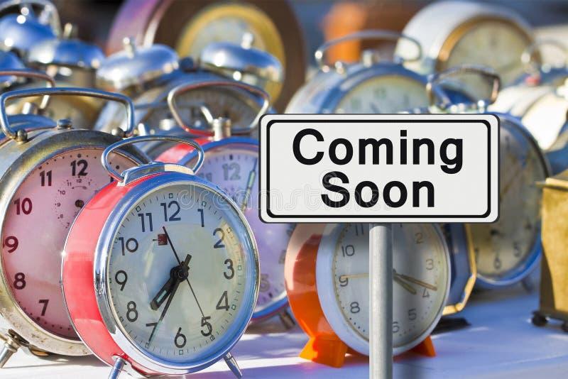 Przychodzący wkrótce szyldowego - pojęcie wizerunek z starego barwionego metalu stołowymi zegarami fotografia royalty free