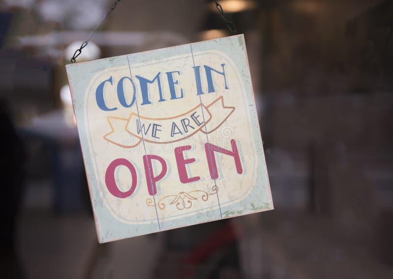 Przychodzimy wewnątrz jesteśmy otwarci podpisujemy wewnątrz sklepowego okno zdjęcia royalty free