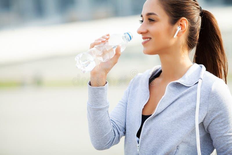 przydatno?? Piękna kobiety woda pitna i słucha muzyka po biegać fotografia stock