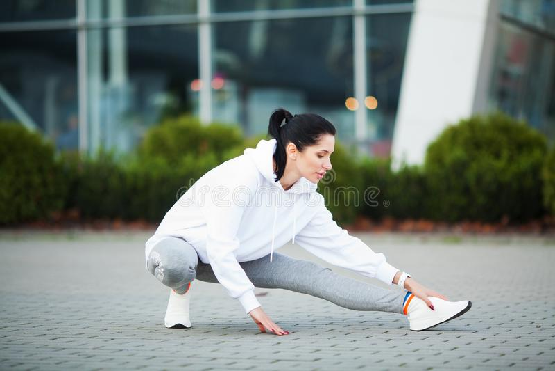 przydatno?? Piękna młoda kobieta robi ćwiczeniom w parku zdjęcie royalty free