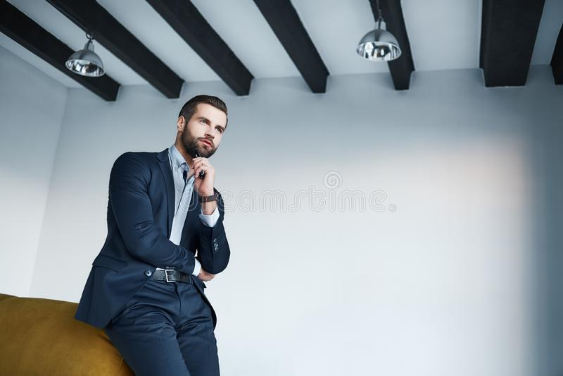 Przyglądający właśnie doskonalić Młody brodaty biznesmen w eleganckim ciemnym kostiumu myśleć o pomyślnej przyszłości fotografia stock