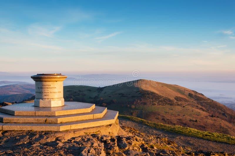 Przyglądający za toposcope na wierzchołku Worcestershire bakan od, przy mglistym, wschód słońca na zima ranku Malvern wzgórza, UK zdjęcie royalty free