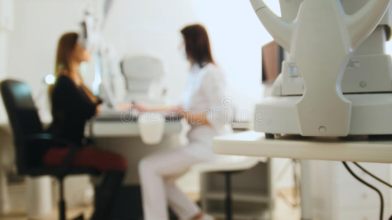 Przygląda się diagnostycznego kliniki pojęcie okulista z tonometer i pacjent -, zamazujący zdjęcie stock