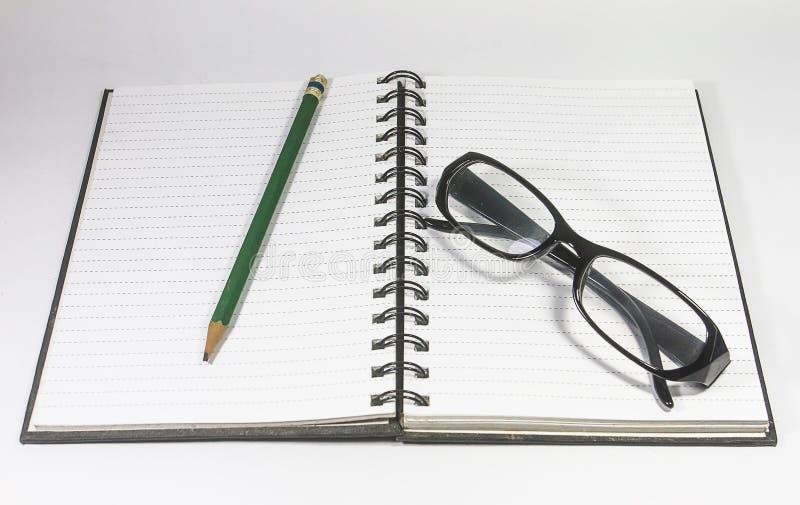Przygląda się szkła z ołówka i segregatoru notatnikiem odizolowywającym na białym tle zdjęcia stock