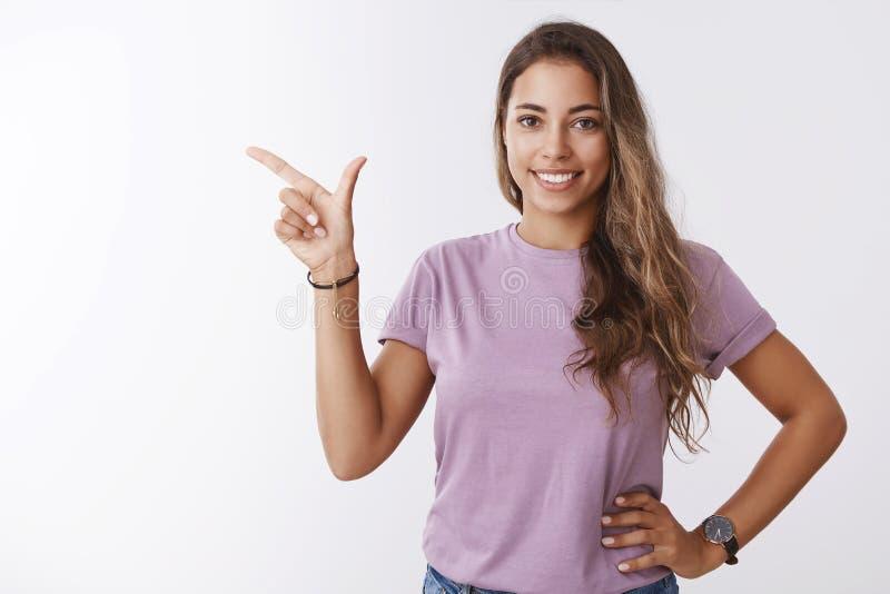 Przyglądająca śliczna szczęśliwa uśmiechnięta europejska dziewczyna trzyma niezobowiązująco relaksującą pozę wskazuje lewą kopii  zdjęcie stock