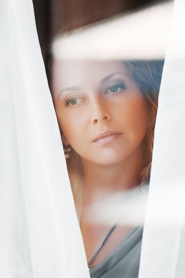 przyglądająca smutna nadokienna kobieta fotografia stock
