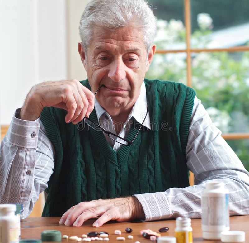przyglądający mężczyzna pigułek seniora stół fotografia stock