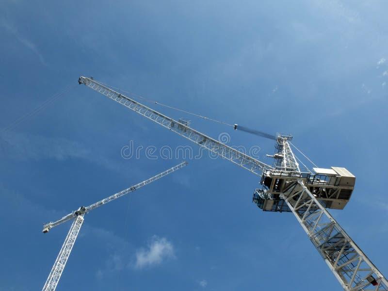 Przyglądający oddolny widok dwa wysokiego białego budowa żurawia na placu budowym przeciw niebieskiemu niebu z chmurami zdjęcie stock
