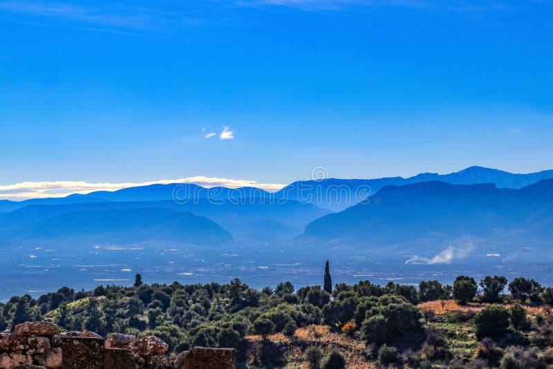 Przyglądający przez Peloponnesus półwysepa w południowym Grecja od ruin antyczny Mycenae blisko półmroku z silnikami wiatrowymi o zdjęcie stock