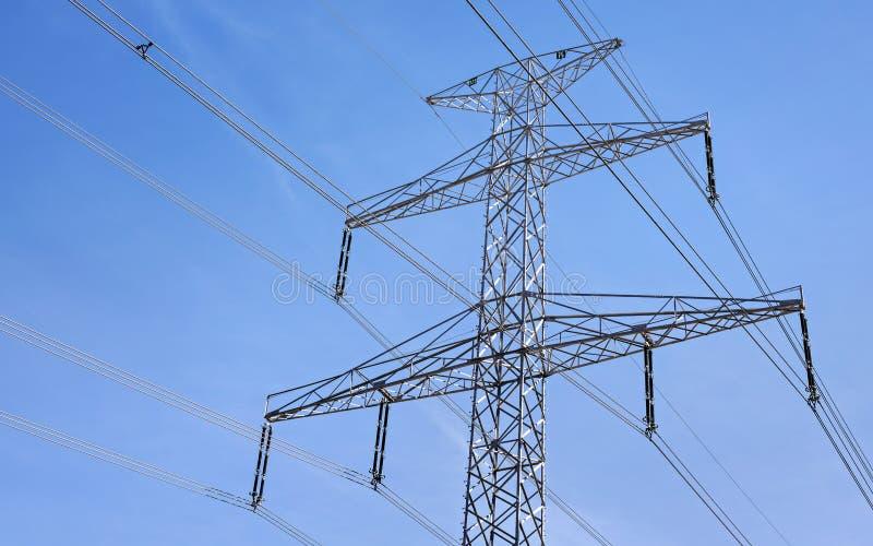 Przyglądający w górę stalowego elektryczność pilonu z kablami, jasny niebo w tle obraz royalty free