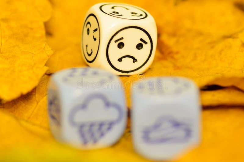 Przygnębiająca i smutna pogoda pokazywać na kostka do gry jesień obraz royalty free