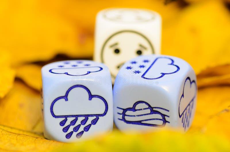 Przygnębiająca i smutna pogoda pokazywać na kostka do gry jesień fotografia stock