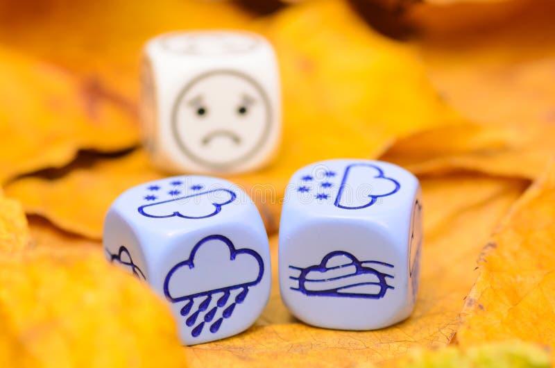 Przygnębiająca i smutna pogoda pokazywać na kostka do gry jesień obrazy stock
