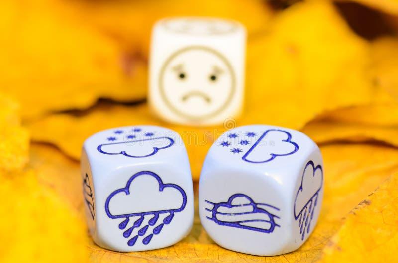 Przygnębiająca i smutna pogoda pokazywać na kostka do gry jesień fotografia royalty free