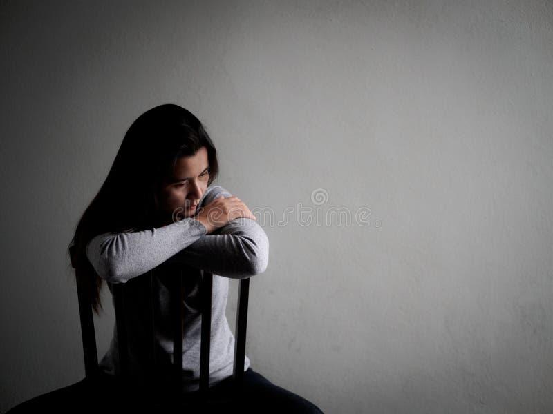 Przygnębiona łamająca hearted kobieta siedzi samotnie na drewnianym krześle zdjęcia royalty free