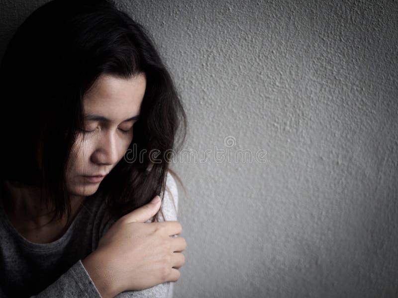 Przygnębiona łamająca hearted kobieta siedzi samotnie w ciemnym pokoju zdjęcie royalty free
