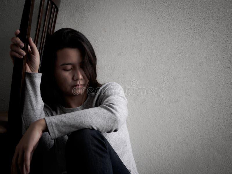 Przygnębiona łamająca hearted kobieta siedzi samotnie w ciemnym pokoju zdjęcia stock