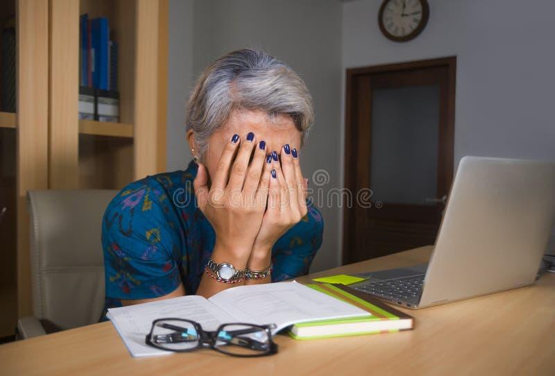 Przygn?biona i zapracowana w ?rednim wieku atrakcyjna Azjatycka kobieta pracuje w stresie na laptopu biurku zakrywa jej twarz p?a fotografia royalty free