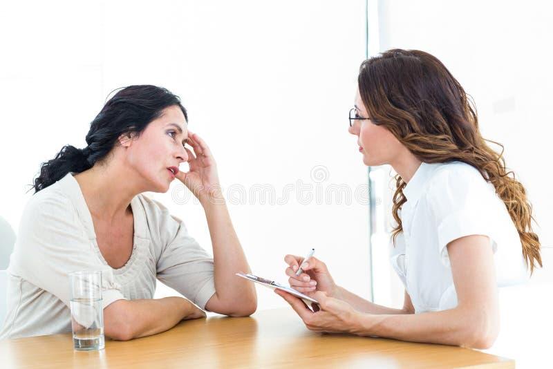 Przygnębiona kobieta opowiada jej terapeuta fotografia stock