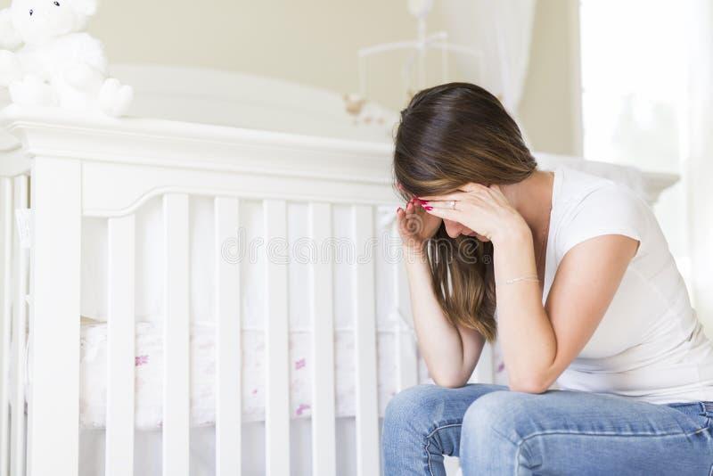 Przygnębiona młoda kobieta w dziecko pokoju obraz royalty free