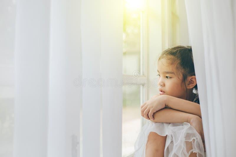 Przygnębiona mała dziewczynka blisko okno w domu, zbliżenie fotografia royalty free