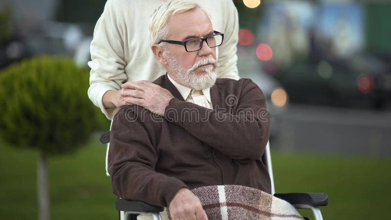 Przygnębiona niepełnosprawna starsza samiec w wózka inwalidzkiego uderzania młodej żeńskiej ręce, rodzina zdjęcie royalty free