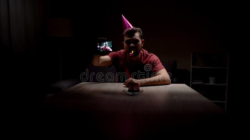 Przygnębionej mężczyzna odświętności urodzinowy samotny, robić selfie w ciemnym pokoju, nędznym zdjęcie stock