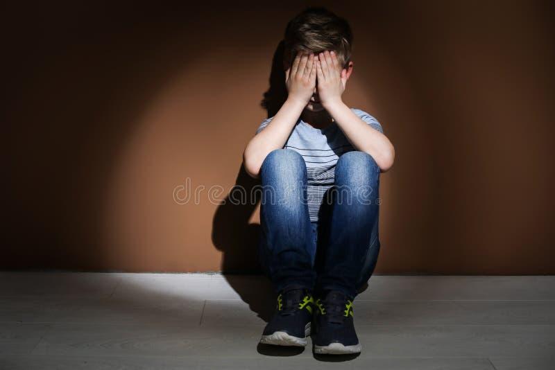 Przygnębiony chłopiec obsiadanie na podłoga Czas odwiedzać dziecko psychologa zdjęcia royalty free