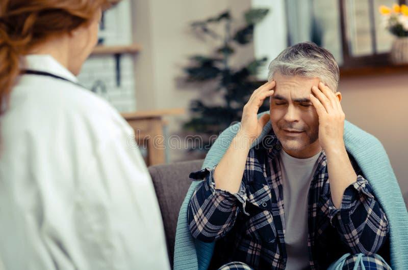 Przygnębiony dorośleć mężczyzny cierpienie od silnej migreny zdjęcie stock