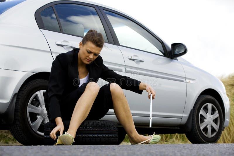 Przygnębiony kobiety obsiadanie przy jej łamanym samochodem fotografia royalty free
