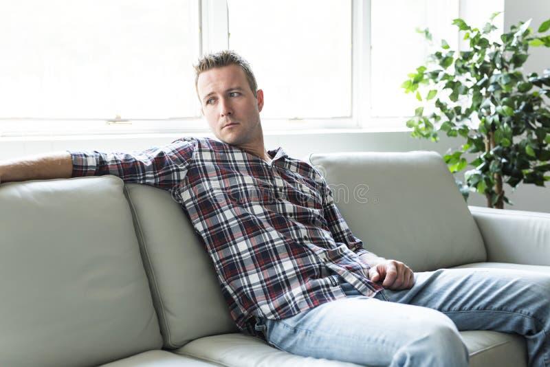 Przygnębiony mężczyzna główkowanie na kanapie samotnie w domu fotografia stock