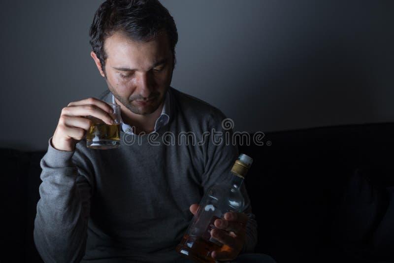 Przygnębiony mężczyzna nadużywać alkohol zdjęcie royalty free