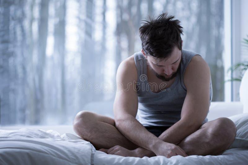 Przygnębiony mężczyzna obsiadanie na łóżku zdjęcia royalty free